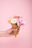 Person holding waffle cone with beautiful blooming flowers isolated on pink Stock Photo