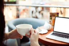 Person Holding White Ceramic Teacup in Front of a Macbook Pro Stock Photo