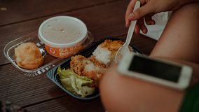 Person Holding White Disposable Spoon Eating Fried Chicken Stock Image