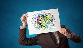 Person holding white paper in front of her head with brain concept. Young person holding white paper in front of her head with colorful brain concept stock images
