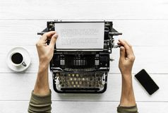 Person Holding White Paper and Typewriter Royalty Free Stock Images