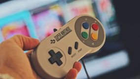 Person Holding White Snes Controller royalty free stock image
