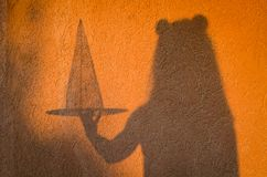 Person holding witch hat for Halloween. Shadow on orange wall of person holding witch hat for Halloween Royalty Free Stock Photography