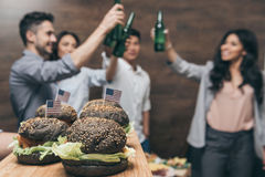 Person holding wooden tray with delicious hamburgers and friends partying behind. Close-up view of person holding wooden tray with delicious hamburgers and Royalty Free Stock Images