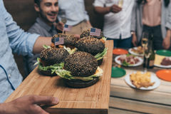 Person holding wooden tray with delicious hamburgers and friends partying behind. Close-up view of person holding wooden tray with delicious hamburgers and Royalty Free Stock Photo