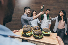 Person holding wooden tray with delicious hamburgers and friends partying behind. Close-up view of person holding wooden tray with delicious hamburgers and Stock Image