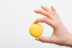 Person holding yellow macaroon Stock Photo