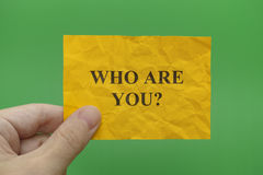 Person holding yellow paper note with question Who are you. In his hand. Green background Royalty Free Stock Images