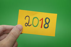Person holding yellow paper note with 2018 year written on it. Green background Stock Images