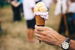 Person Holding Yellow and Purple Ice Cream Royalty Free Stock Images