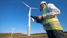 A person holds a clipboard while walking near wind turbines. Renewable electririty, green energy concept. stock footage