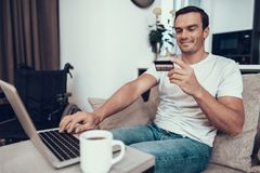 Person Holds Credit Card deficiente e portátil dos usos foto de stock royalty free