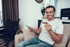 Person Holds Credit Card deficiente e tabuleta dos usos imagens de stock royalty free
