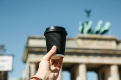 A person holds a disposable cup with coffee or another drink on the background of the Brandenburg Gate in Berlin. A person holds a disposable cup with coffee or royalty free stock photos