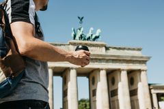 A person holds a disposable cup with coffee or another drink on the background of the Brandenburg Gate in Berlin. A person holds a disposable cup with coffee or royalty free stock images