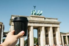 A person holds a disposable cup with coffee or another drink on the background of the Brandenburg Gate in Berlin. A person holds a disposable cup with coffee or royalty free stock image