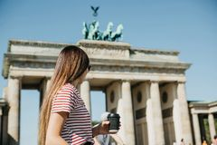A person holds a disposable cup with coffee or another drink on the background of the Brandenburg Gate in Berlin. A person holds a disposable cup with coffee or stock photography
