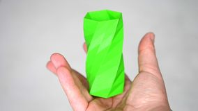The person holds on his hands and view an object created on the 3d printer. The person holds on his hands and view green object created on 3d printer. POV, point stock footage