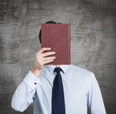 A person holds a red book in front of the head. Royalty Free Stock Photo