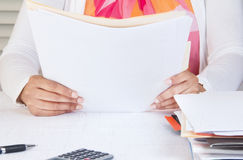 Person in home office reading documents. Professional in office reading through pile of documents royalty free stock image
