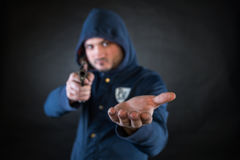 A person in a hoodie is aiming and holding the other hand. Royalty Free Stock Photos
