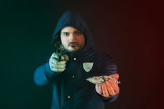 A person in a hoodie is aiming and holding the other hand with the dollar note. Stock Images