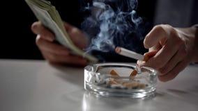 Person i dräkten som räknar pengar och röker cigaretten, olagligt affärsavtal royaltyfri bild
