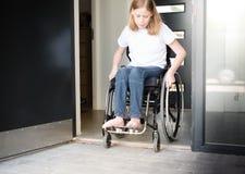 Person i en rullstol som flyttar sig över en låg tröskel Arkivbild