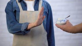 Person i förkläde som gör en gest inget socker i att laga mat, risk av sockersjuka och fetma lager videofilmer