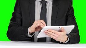 Person i formellt dräktsammanträde på tabellen och bruksbärbara datorn grön skärm arkivfilmer