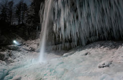 Person illuminating frozen waterfall. Icicles hanging at Pericnik Slap, Vrata valley in Slovenia Stock Images