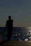 Person im Schattenbild auf Pier-Fischen Lizenzfreie Stockfotos