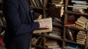 Person im schwarzen Marineanzugs-Holdingbuch in seinen Händen stockfotografie