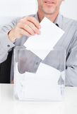 Person inserting ballot in box Stock Image