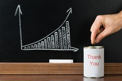 Person inserting coin in thank you can Stock Photos