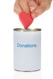 Person inserting heart in donation can Stock Images