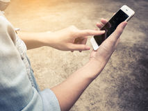 Person in jean jacket using mobile phone. Close-up of person in jean jacket using mobile phone outdoor, Vintage Filter Royalty Free Stock Photo
