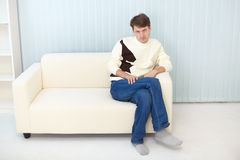 Person in jeans and sweater sits on sofa Royalty Free Stock Images