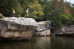 Person Jumping do penhasco no lago Fotos de Stock