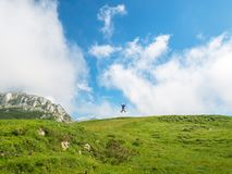 Person jumping for joy and celebrating victory in nature. In the meadow and mountains stock photo