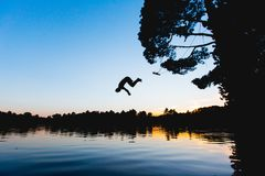 Person Jumping on Lake Silhouette Photograph Stock Photos
