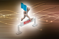 Person jumping over word risk with flag Stock Photos