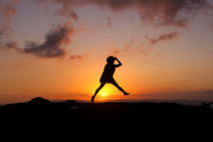 Person Jumping during Sunset on Low Angle View Photography Stock Image
