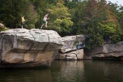 Person Jumping von der Klippe in See Stockfotos