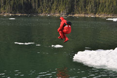 Person jumping into the water with a survival suit Royalty Free Stock Image