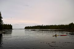 Person kayaking in a tranquil bay at sunrise Stock Image