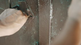 Person key opens the lock. On the heavy iron door stock video
