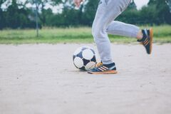 Person Kicking Soccer Ball on Gray Sand Stock Image