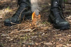 Person kindles fire in the forest. Person warms himself by the fire in the forest. Hunter in the autumn forest Stock Photos