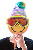 Person with knitted hat and ski mask hiding her face behind a smiley. Person with knitted hat and ski mask hiding her face behind an happy smiley Royalty Free Stock Photo
